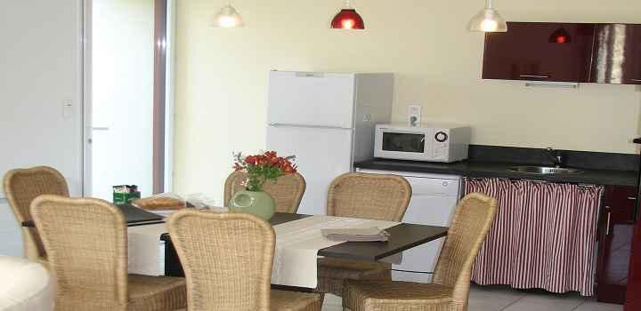 Vue de la cuisine, la table et la porte d'entrée de la location maison de vacances avec piscine en vendée